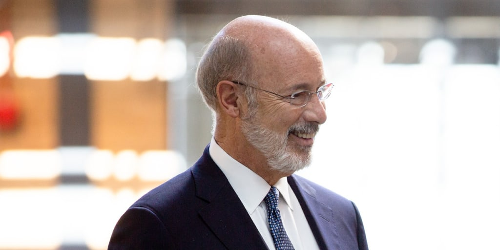 Image of Governor Tom Wolf standing next to a row of windows.