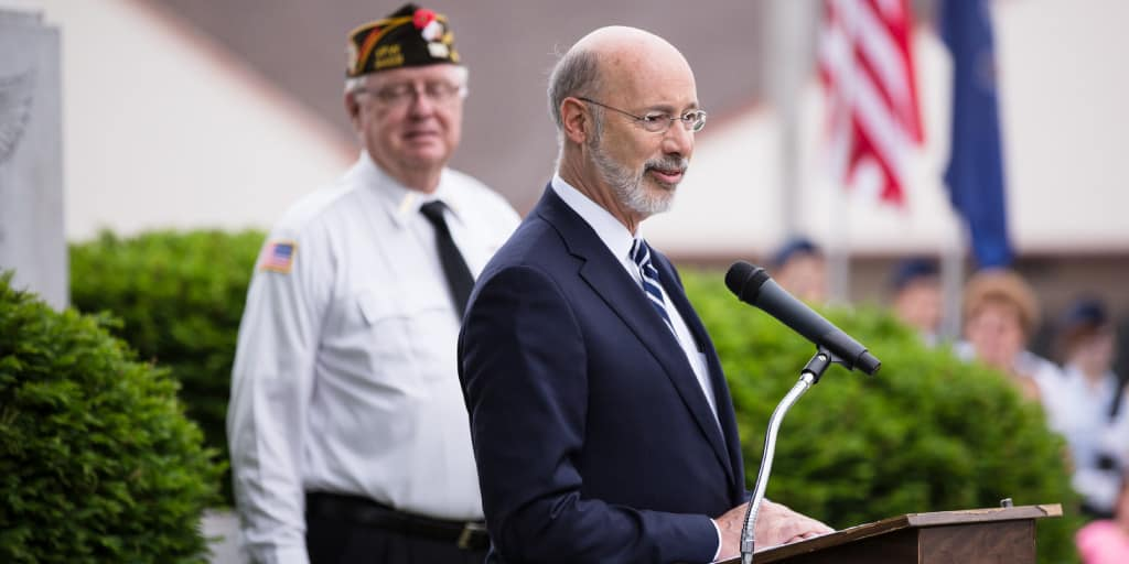 Image of Governor Tom Wolf speaking behind a podium next to a veteran.