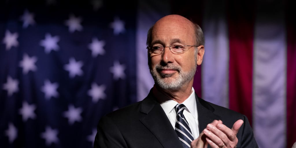 Image of Governor Tom Wolf applauding next to a the United States flag.