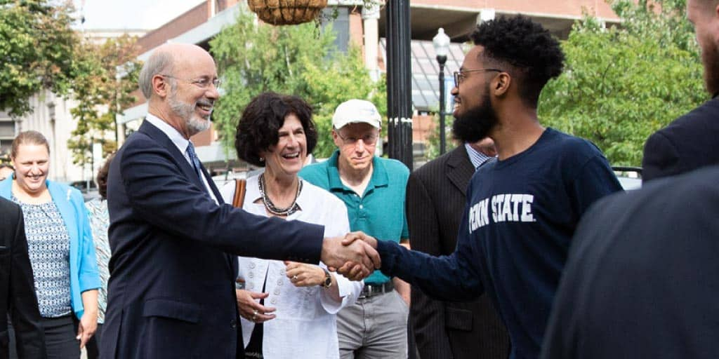 Image of Governor Wolf shaking hands with a pedestrian.