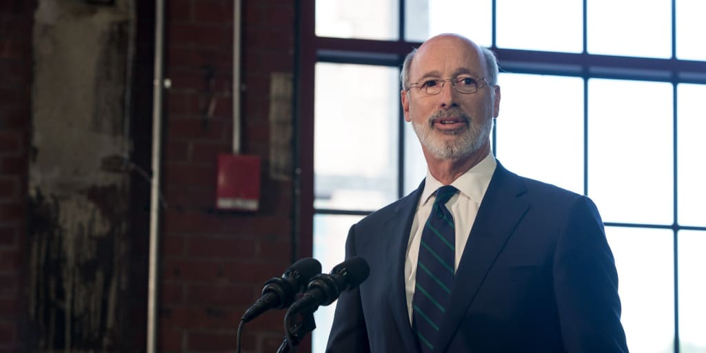 Image of Governor Tom Wolf speaking next to a large industrial building window.