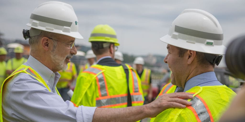 Image of Governor Tom Wolf speaking to someone in construction uniform.