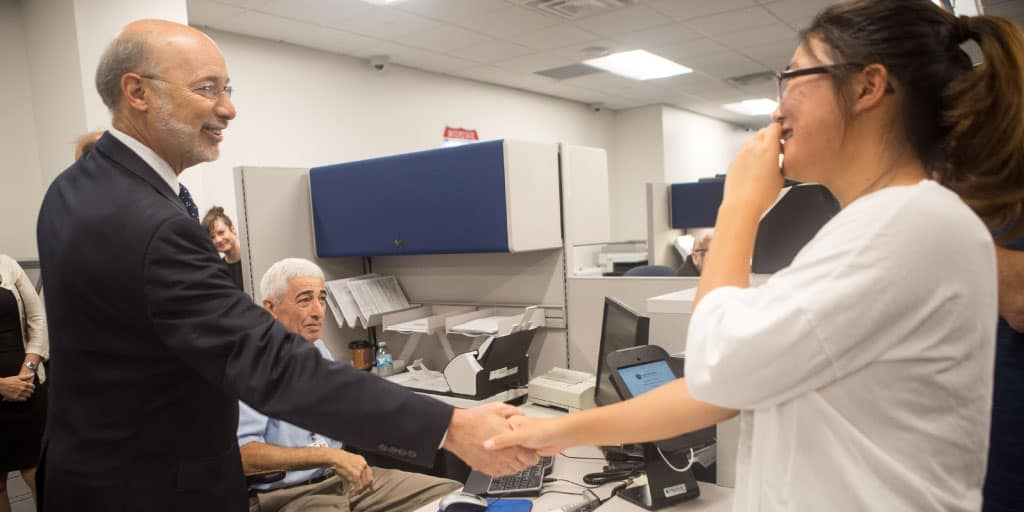 Image of Governor Tom Wolf shaking hands with someone at a drivers' license center.