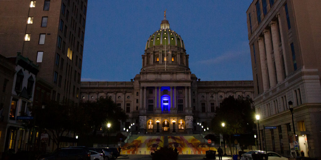 Image of the State Capitol at night with single blue light.