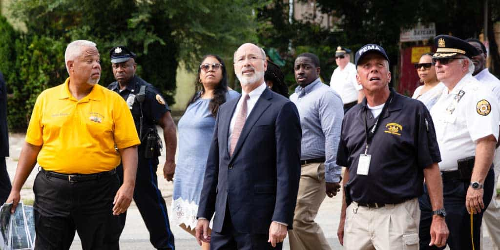 Image of Governor Wolf and a crowd walking outside and looking up at storm damage.