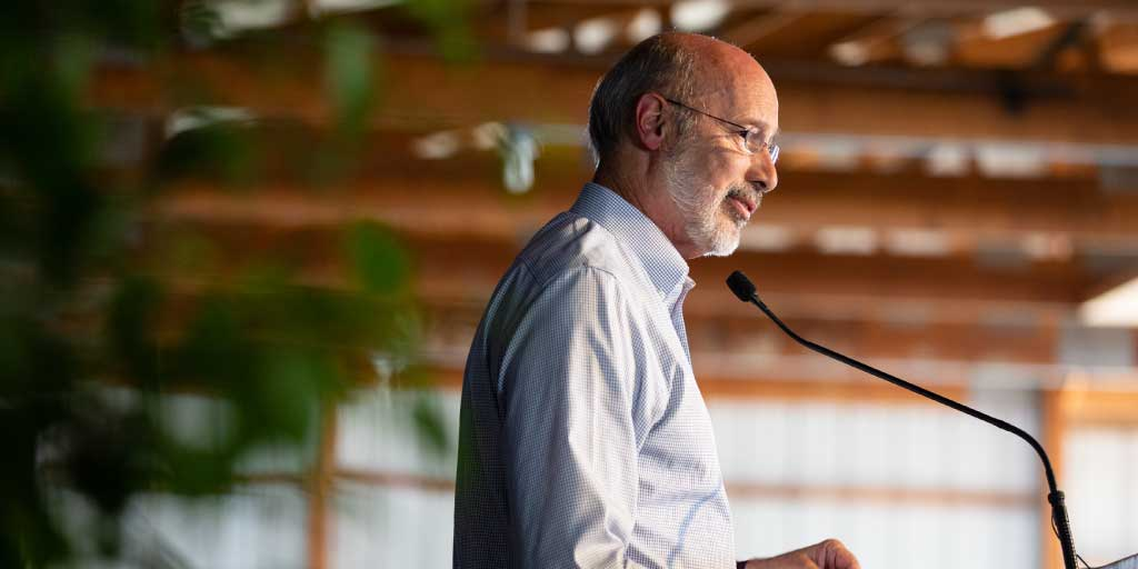 Image of Governor Tom Wolf speaking into a microphone at a podium.