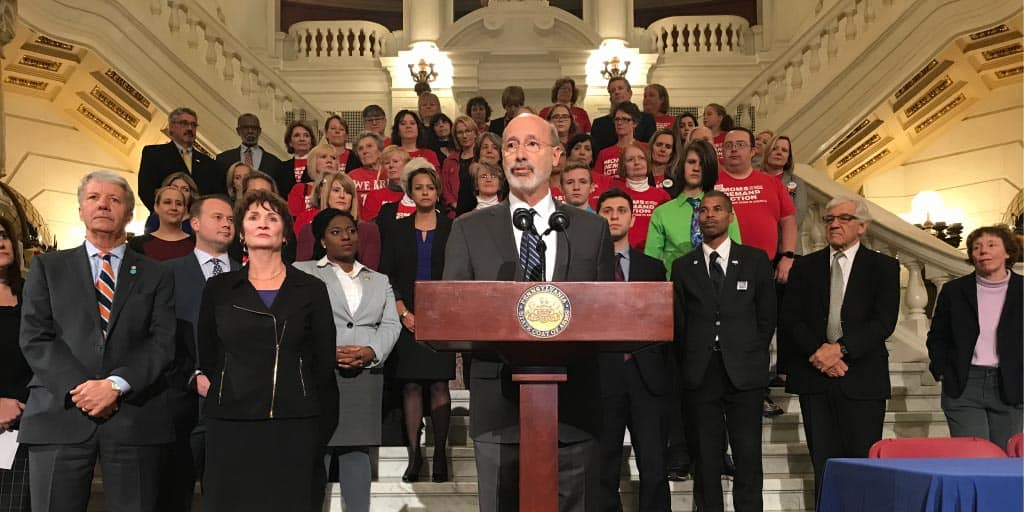 Image of Governor Tom Wolf speaking at a podium on the steps of the main lobby of the Capitol building.