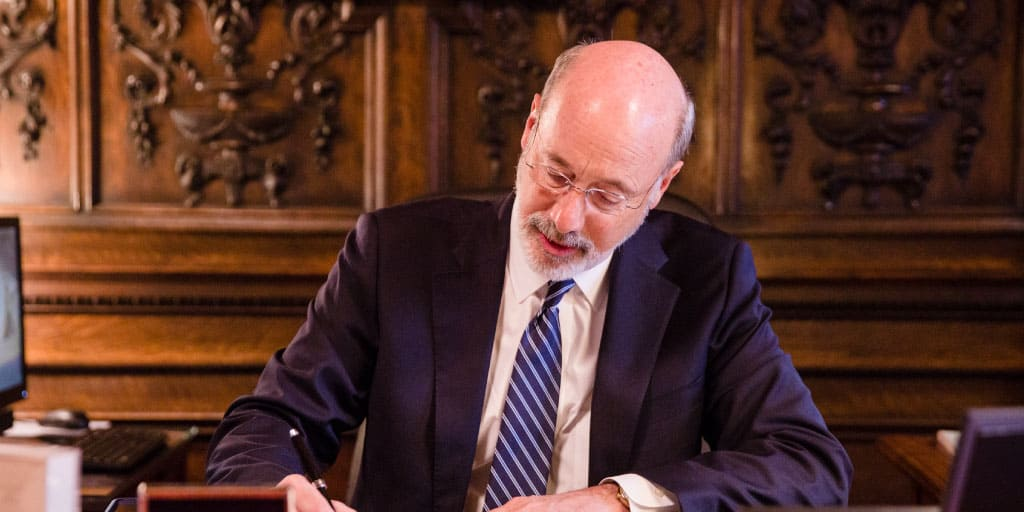Image of Governor Tom Wolf signing an executive order at his desk.