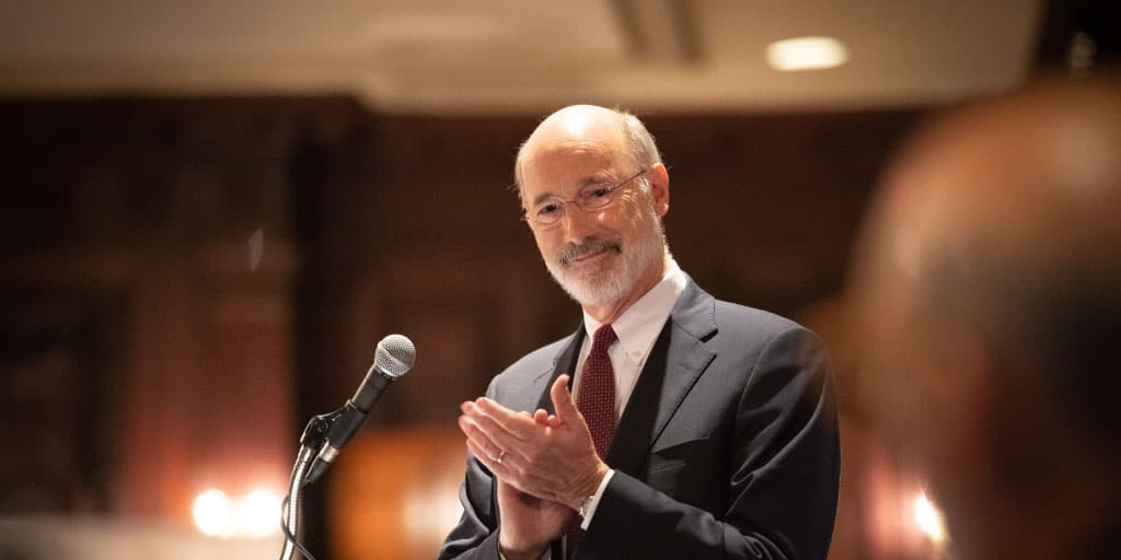 Image of Governor Tom Wolf standing behind a podium smiling and clapping.