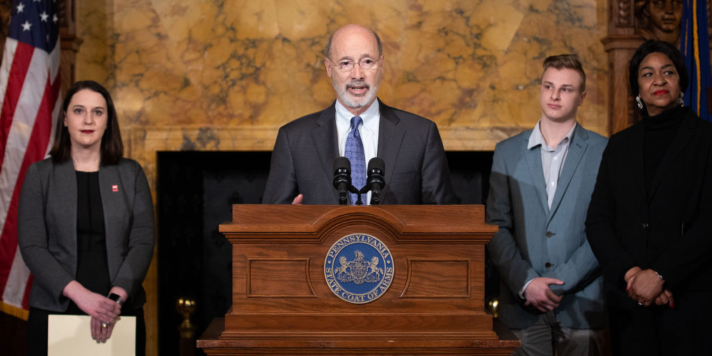 Governor Tom Wolf speaking at a podium in the Reception Room.