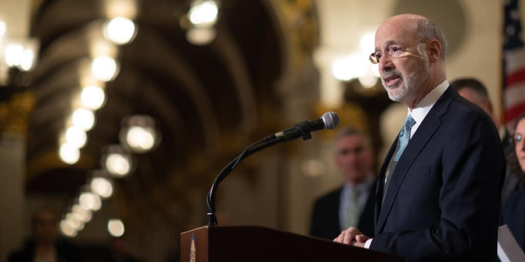 Governor Tom Wolf speaking at a podium.