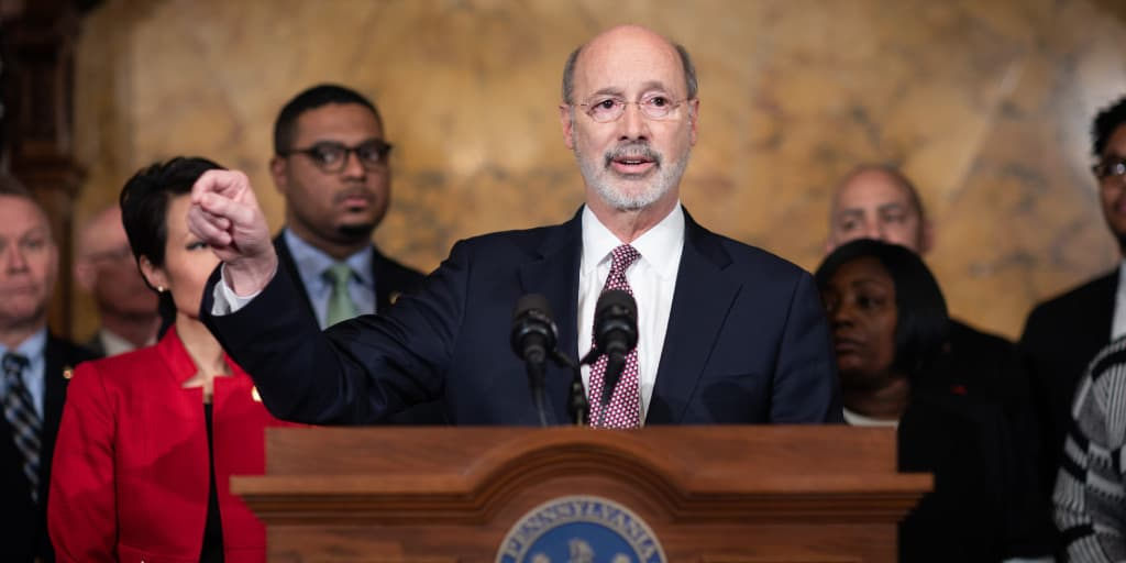 Governor Tom Wolf speaking at a podium on minimum wage.