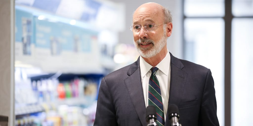 Governor Tom Wolf speaking at a podium in a pharmacy.
