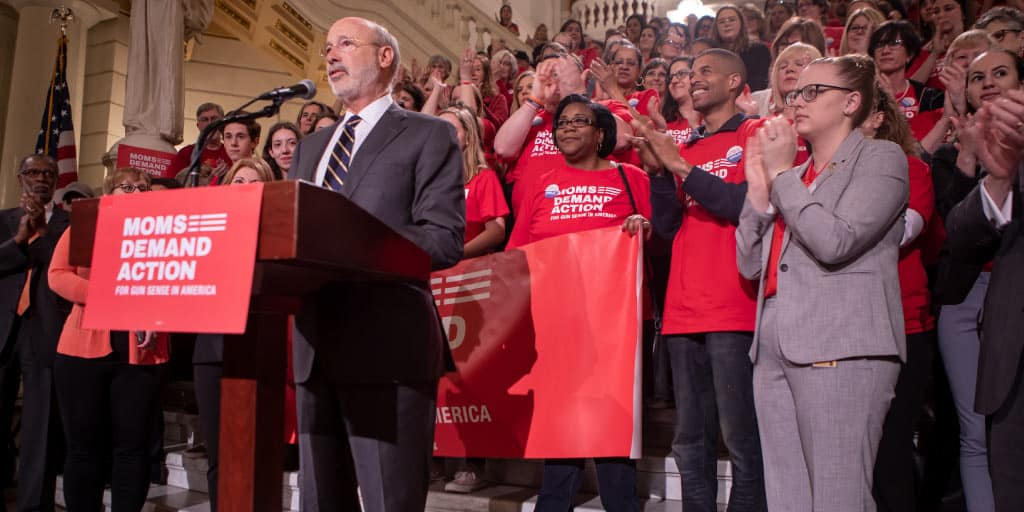 Governor Tom Wold speaking at a podium in front of the Capitol steps with Moms Demand Action members behind him.
