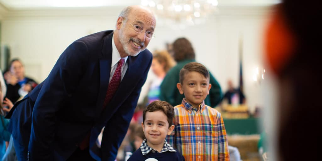 Governor Tom Wolf taking a photo with two boys.