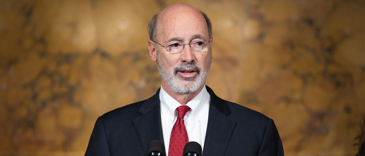 Governor Tom Wolf stands and speaks from a podium