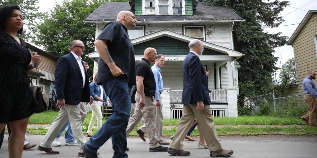 Governor Wolf and Fetterman walking with officials walking in a neighborhood.