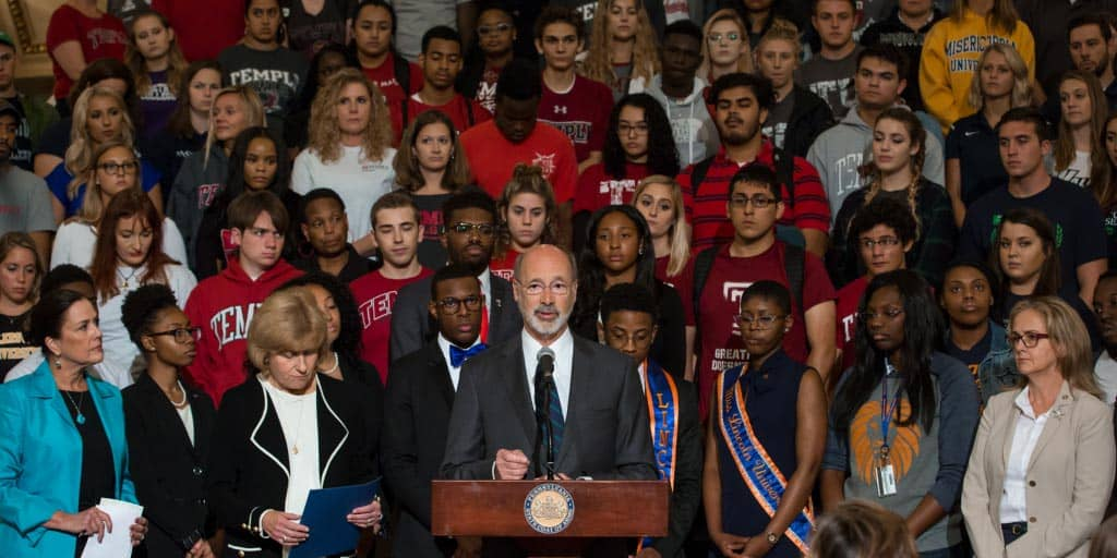 Governor Wolf speaking in the Capitol with a large group of students behind him.