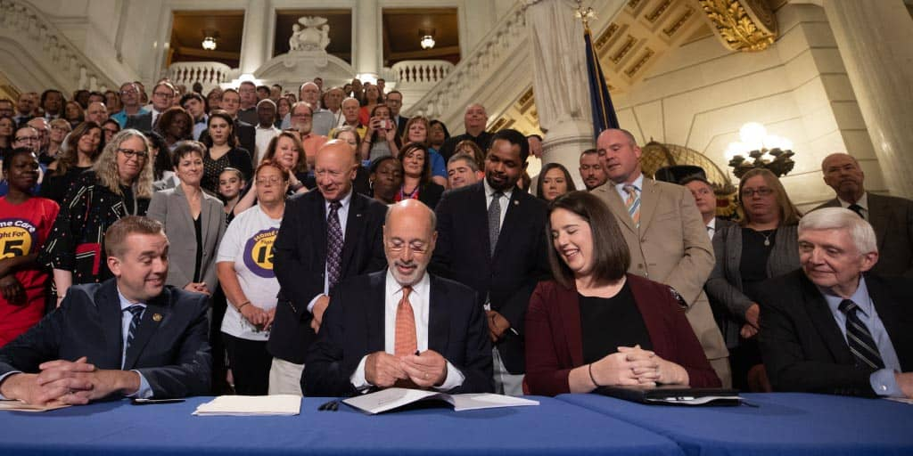 Governor Wolf signing HB 3 with officials and supporters behind him.