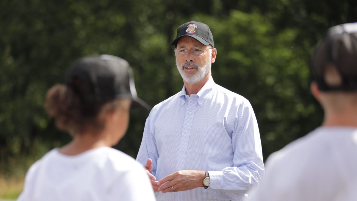 Governor Wolf wears a PA State Police hat as he speaks to campers