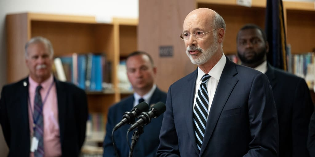 Governor Wolf speaking with officials behind him in a library.