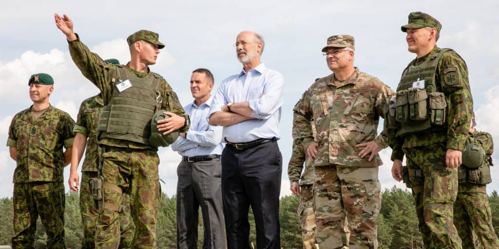 Governor Wolf standing between National Guard troops in Lithuania.