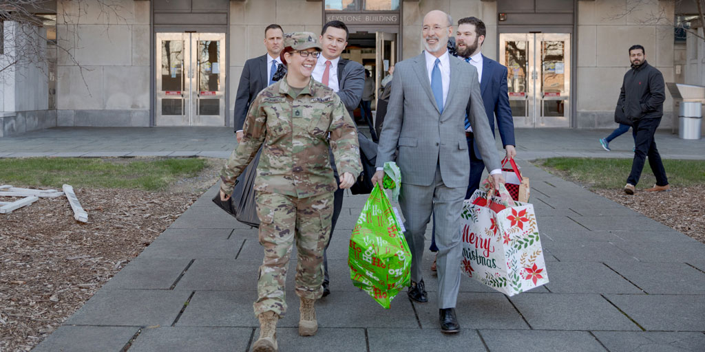 Governor Wolf carries presents with a PA National Guard Member.