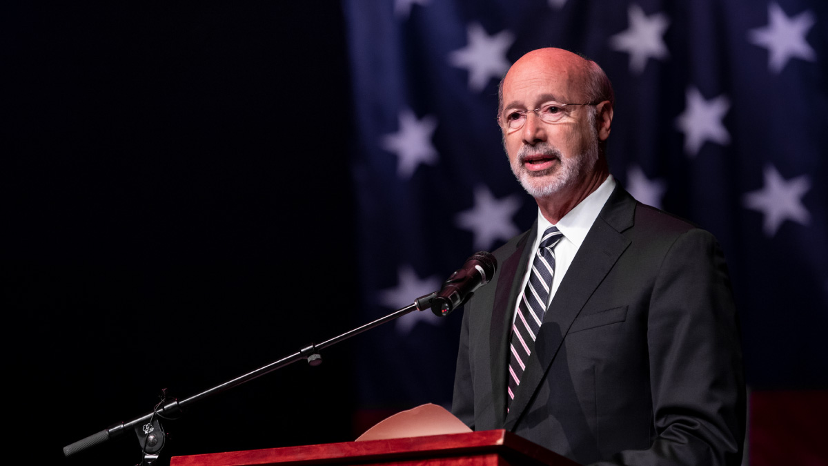 Governor Tom Wolf speaking in front of the American flag