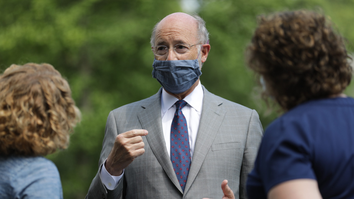 Governor Tom Wolf speaking with hospital staff while wearing a mask.