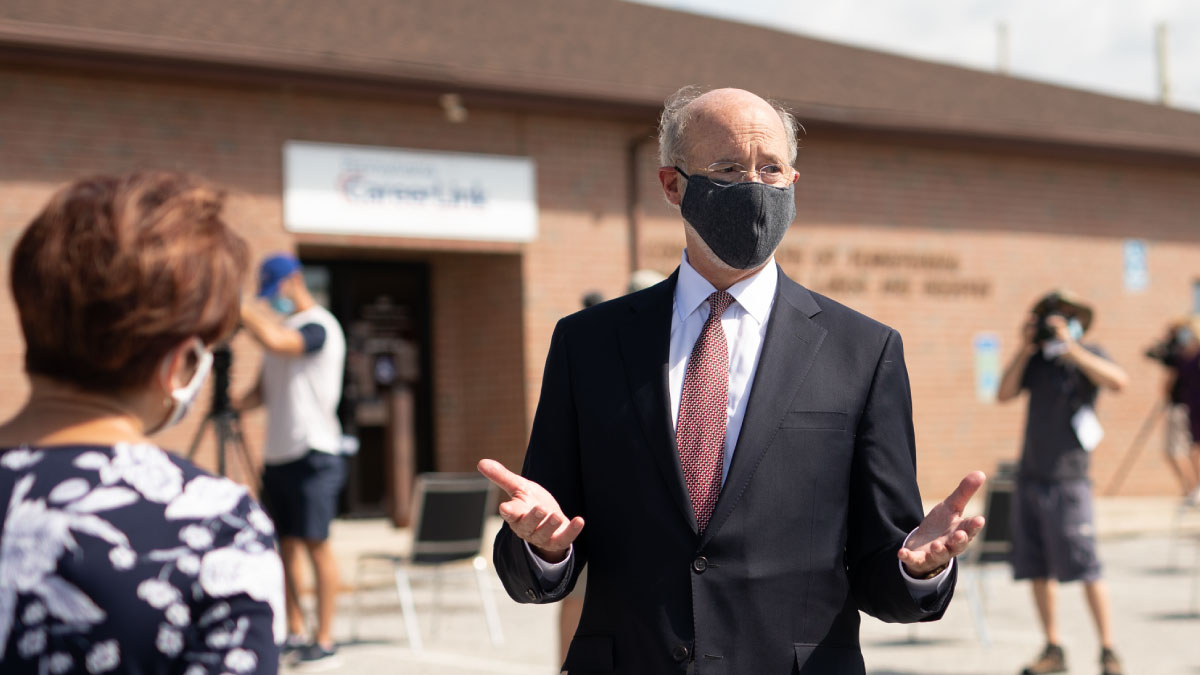 Image of Governor Tom Wolf standing outside and wearing a mask