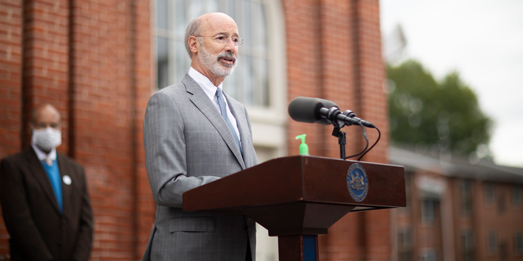 Governor Tom Wolf speaking at a podium outside of a brick building