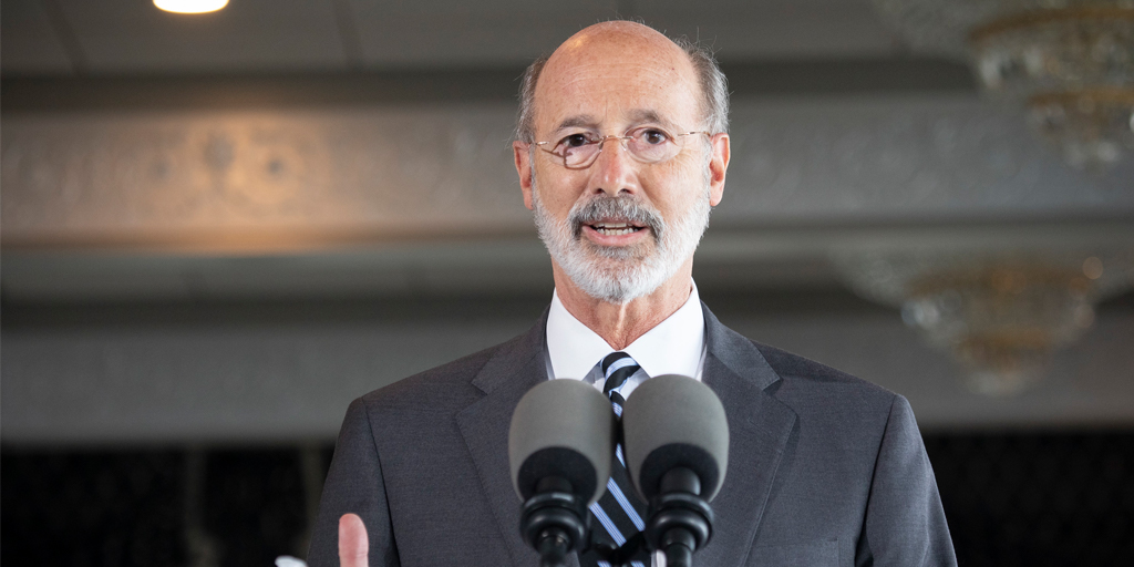Governor Tom Wolf speaking inside a restaurant with chandeliers in the background
