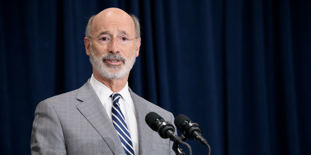 Governor Tom Wolf speaking inside with a blue curtain in the background
