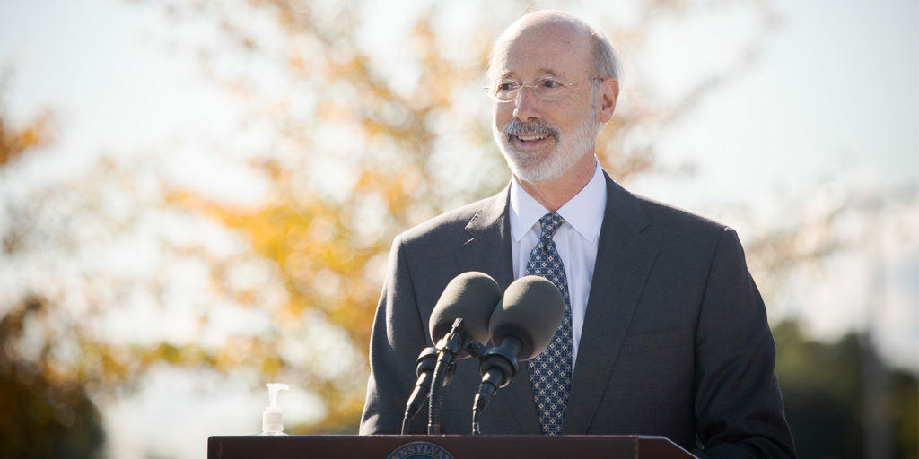 Governor Tom Wolf speaking outside at a podium with fall trees in the background