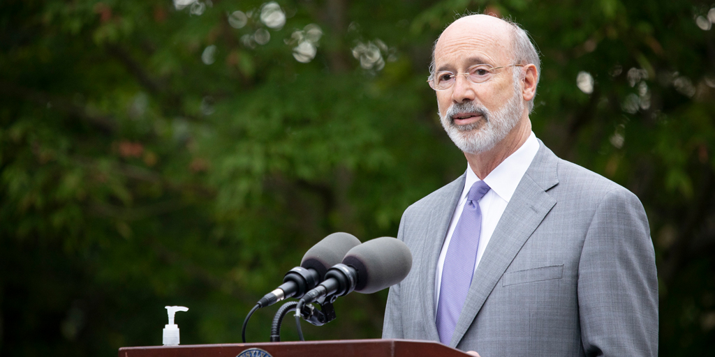 Governor Tom Wolf speaking outside at a podium with trees in the background