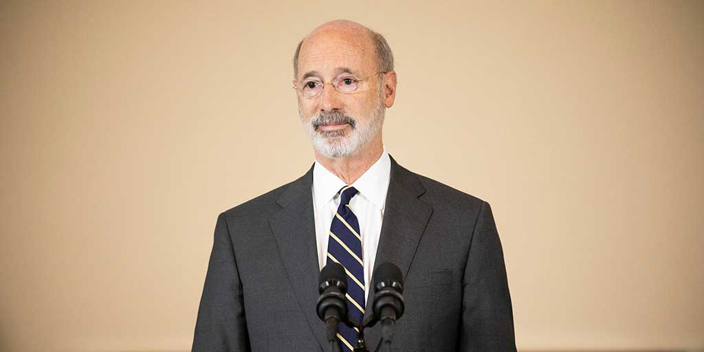 Governor Tom Wolf in front of a tan wall
