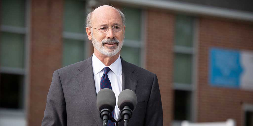 Governor Tom Wolf outside in front of a building