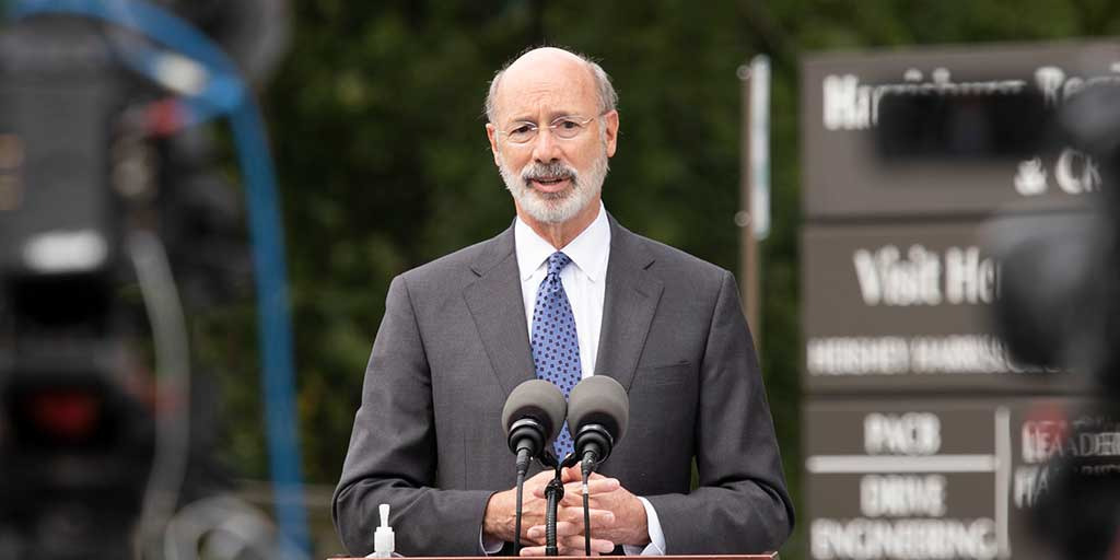 Governor Tom Wolf outside with trees and a sign in the background