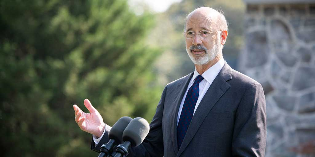 Governor Tom Wolf speaking outside with his hand raised