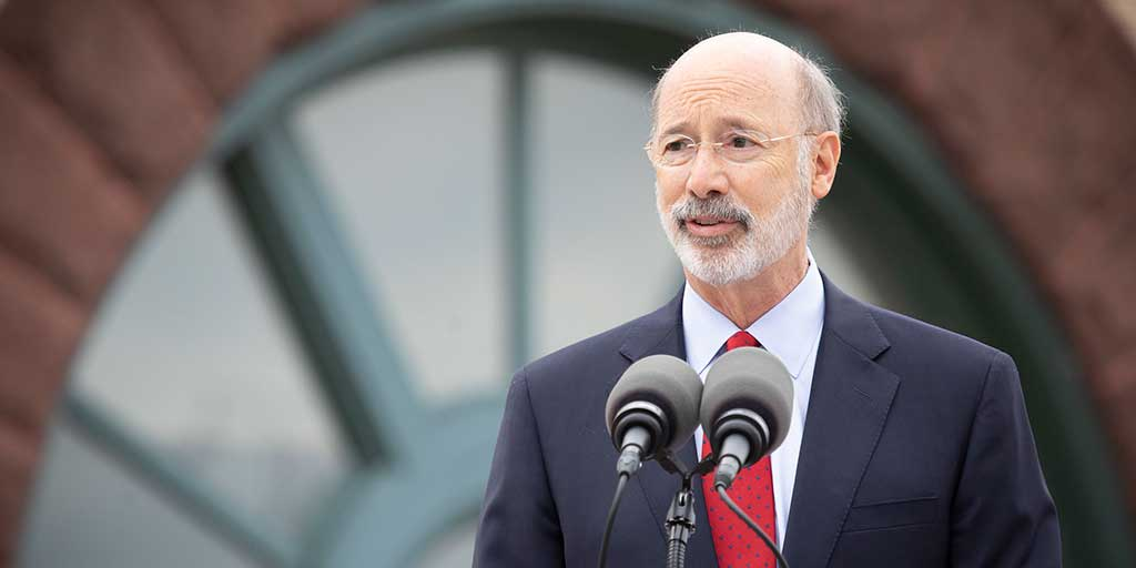 Governor Tom Wolf speaking in front of a building