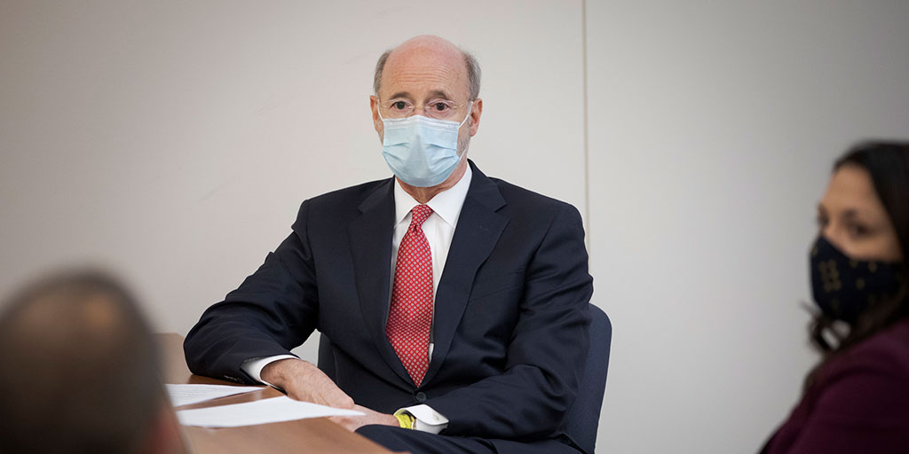 Governor Tom Wolf sitting at a table with a mask on speaking to two people