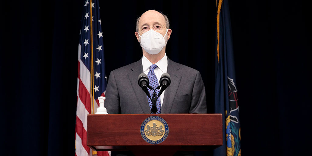 Governor Tom Wolf standing at a podium with a mask on with flags in the background
