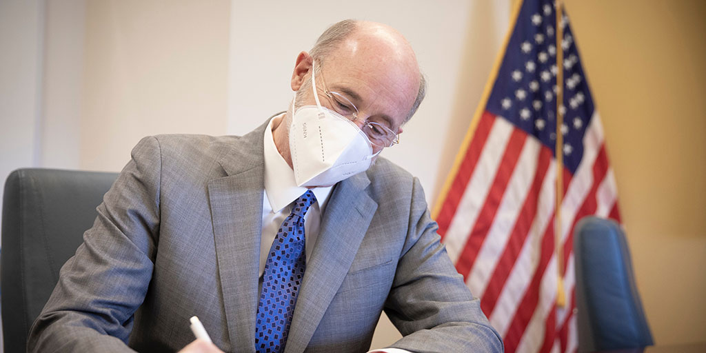 Governor Tom Wolf signing a bill with a mask on