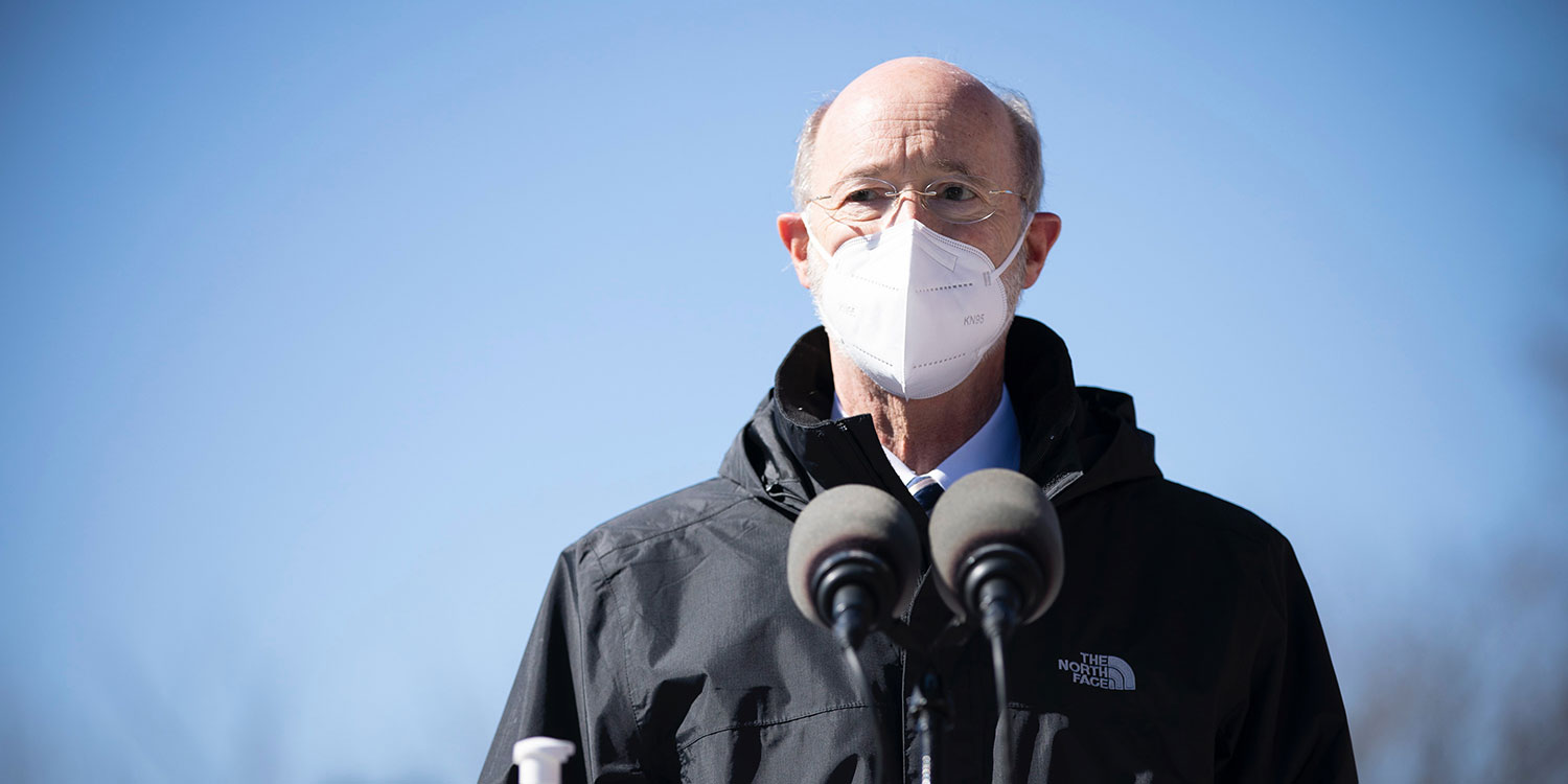 Governor Tom Wolf speaking outside with a mask on
