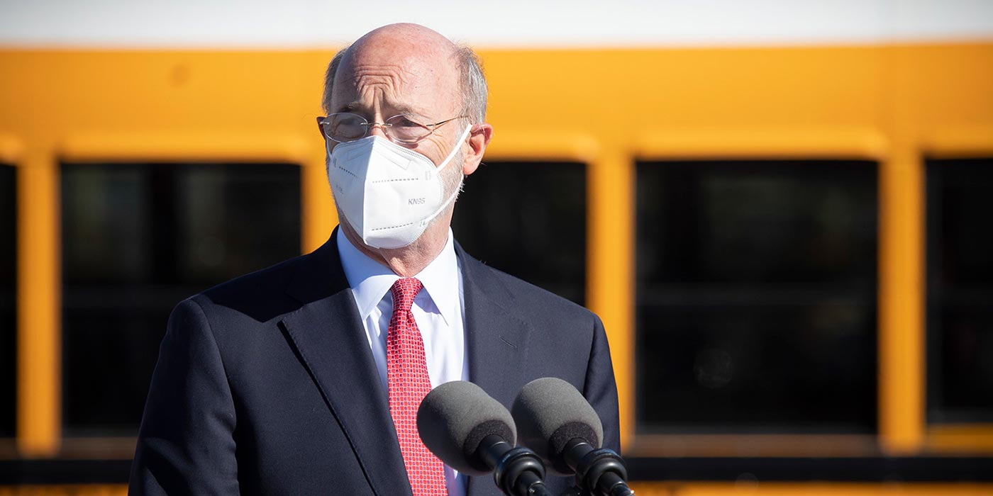 Governor Tom Wolf at a podium in front of a bus