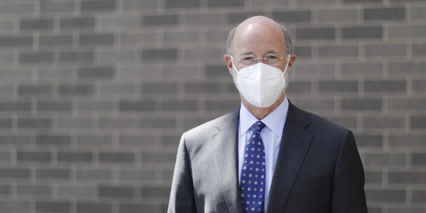 Governor Tom Wolf wearing a mask against a brick wall