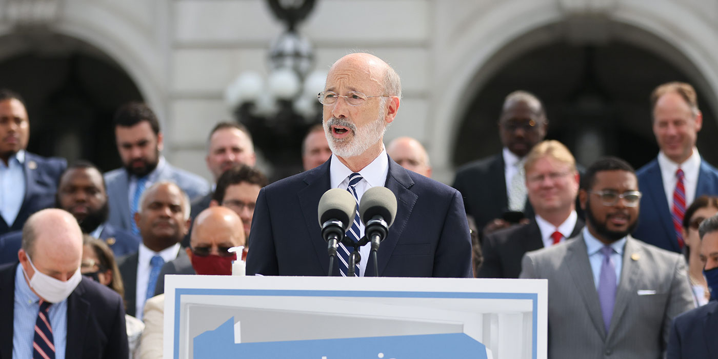 Governor Tom Wolf speaking in front of PA Democrats