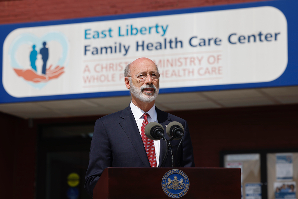 Governor speaking at podium outside health care center