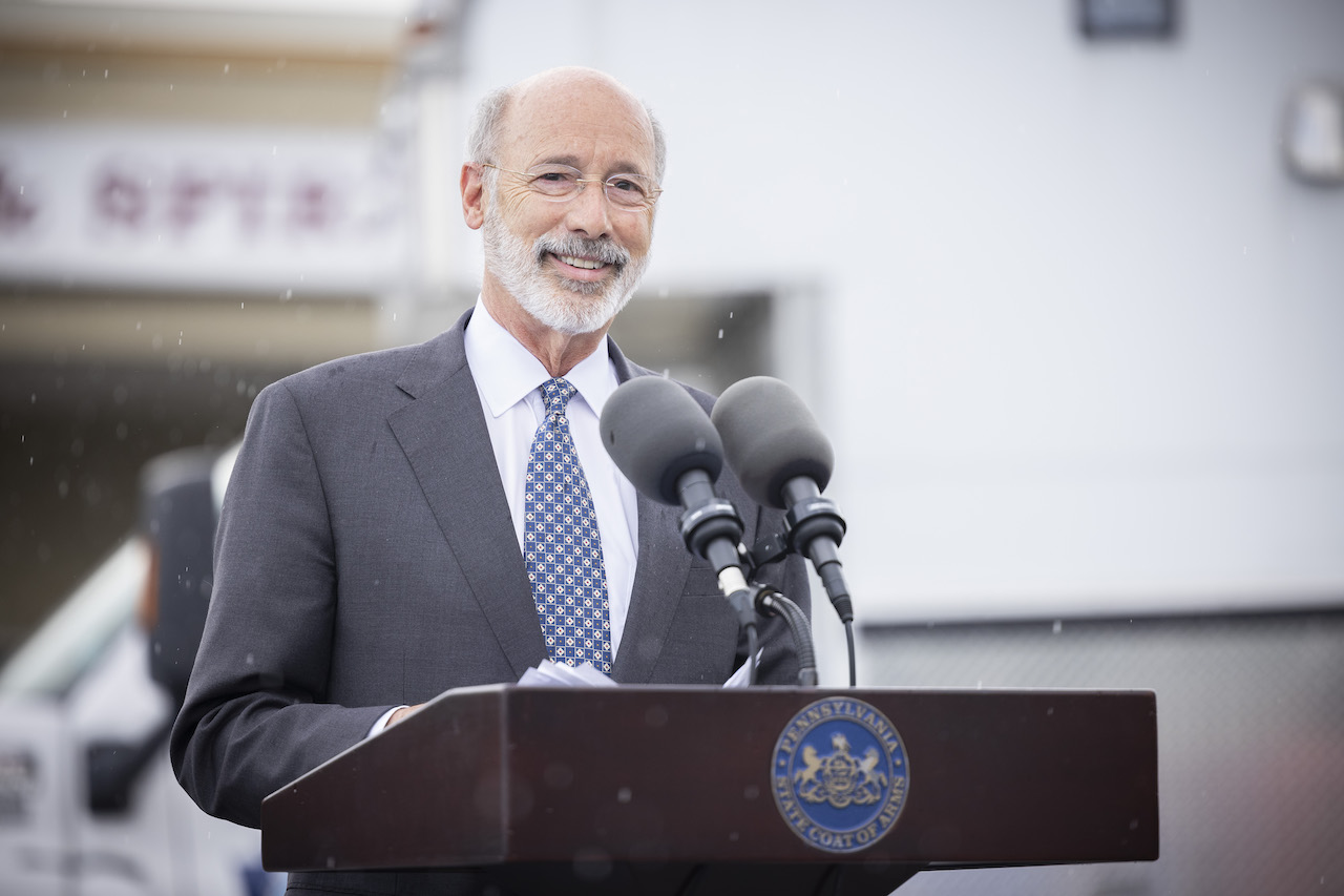 Governor Wolf smiling at podium outside in the rain