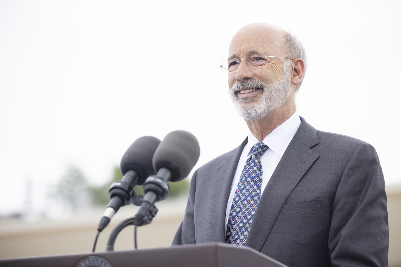 Governor Wolf smiling at podium outside